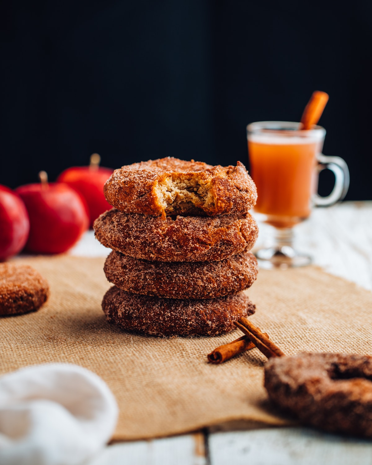 Julianna Vezza's apple cider donuts sit next to a glass of apple cider and fresh apples on a cloth.