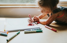 child drawing a picture in her notebook
