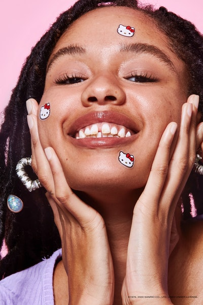 A person smiling with Starface x Hello Kitty stickers on their face