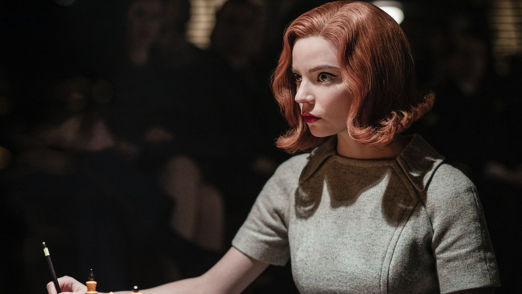 Beth Harmon (Anya Taylor-Joy) stares at her opponent while sitting in front of a chess board in 'The Queen's Gambit.'