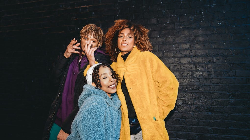 Three friends dancing in the city against a black brick wall