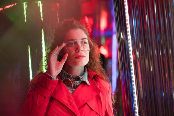 Night portrait of a beautiful young woman with eyeglasses under the colorful neon lights