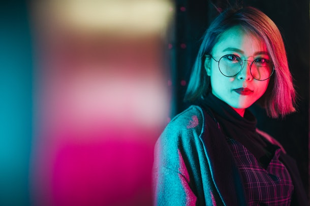 Young woman lit up by neon lights