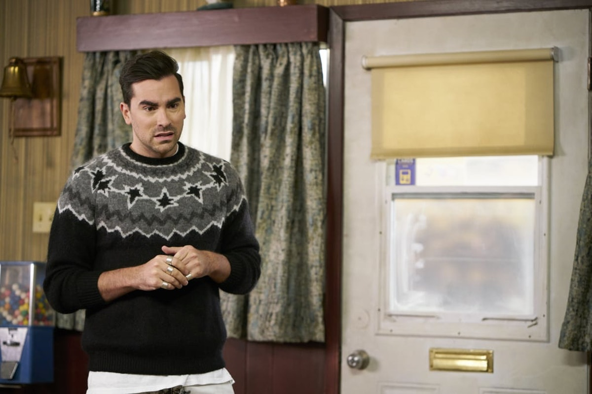 David Rose (Dan Levy) stands in the Schitt's Creek Motel wearing a black and grey sweater.