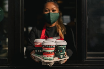 A woman with brown hair and eyes, wearing a green face mask, holding four Starbucks cups in a tray, leaning out to a car through a drive through window.