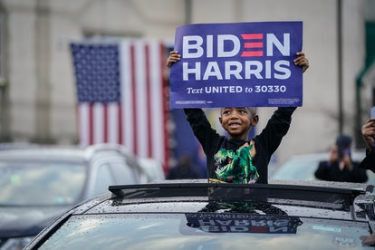 A young Black boy stands with his upper body visible through the sun roof of a car. He is wearing a dinosaur shirt and holding aBiden Harris sigh high over his head.