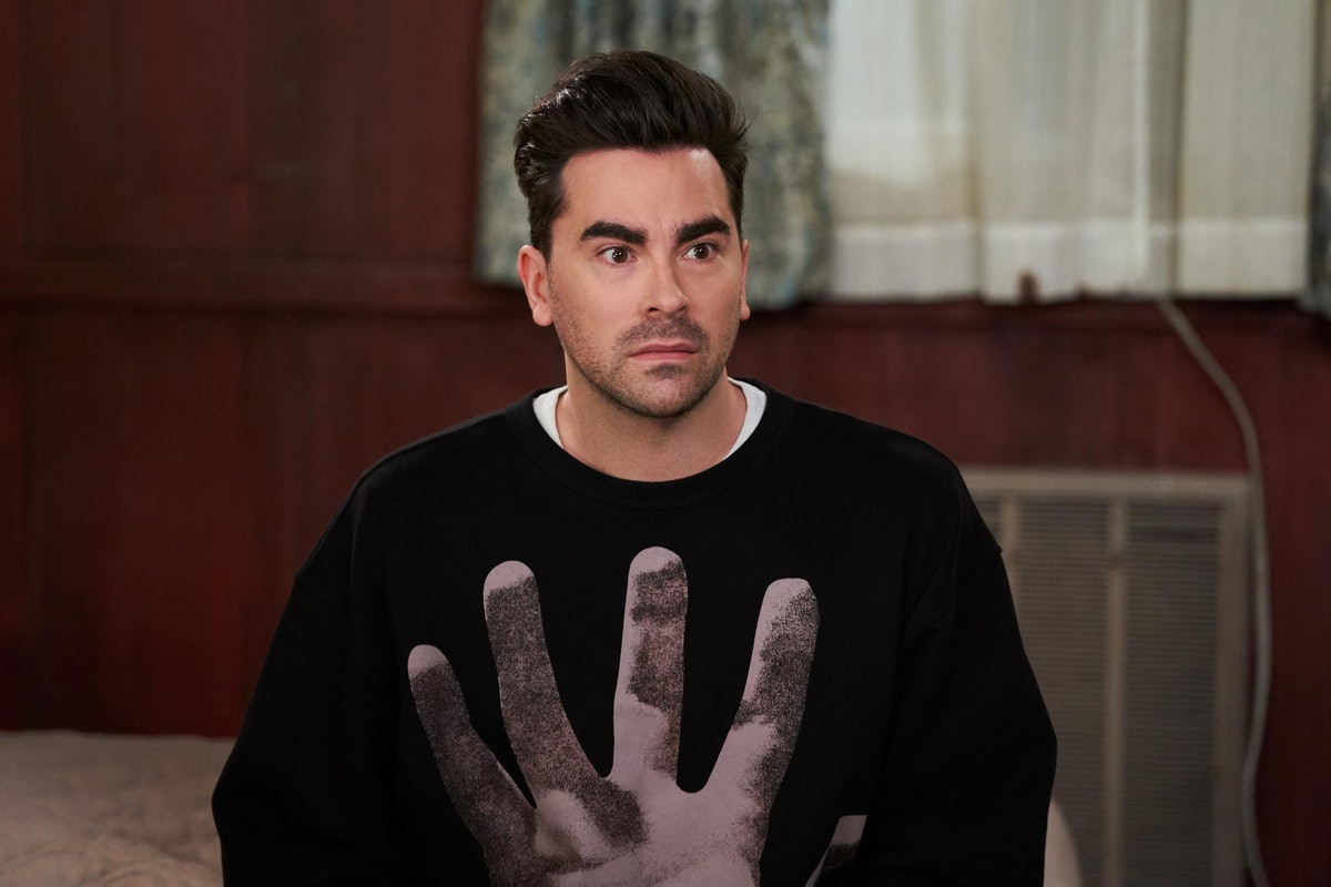 David Rose (Dan Levy) sits on a bed in the Schitt's Creek Motel.