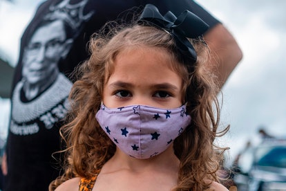 A little girl with curly brown hair wears a lavender face mask with stars looks directly at the viewer. Behind her is a person wearing a black shirt with Ruth Bader Ginsberg's photo in white.