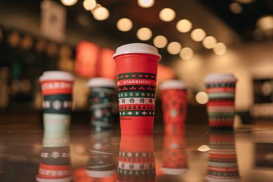 An image of a red Starbucks cups with Christmas trees and snowflakes on the exterior with four additional Starbucks' holiday cups in the background, partially blurred.