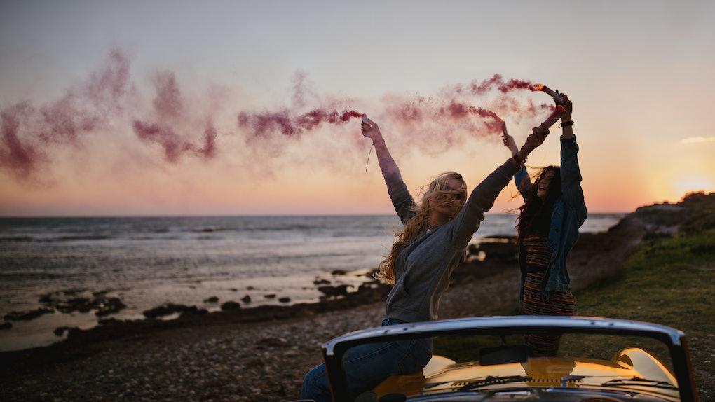 Hipster women having fun with smoke bombs at beach