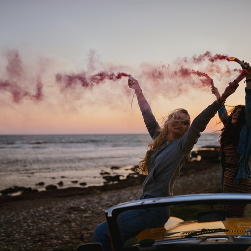 Hipster women having fun with smoke bombs at beach