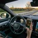 A person behind the wheel of a Volvo S90 Facetiming on their phone,