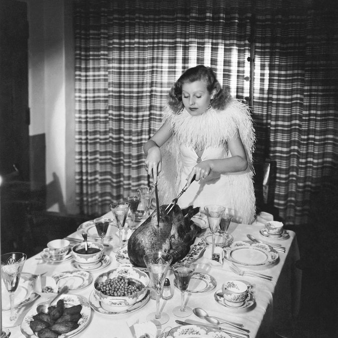 Fox actress Lillian Harvey carves the turkey for a Thanksgiving dinner, Hollywood, California, early 1930s.