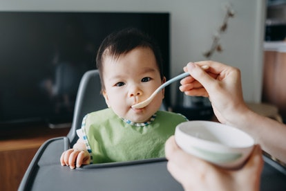 baby eating pureed food in high chair