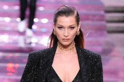 Bella Hadid, with slicked back hair, walks the runway
