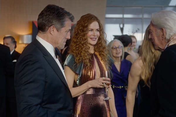 The Cast of 'The Undoing' smiles and chats at a fancy cocktail party.