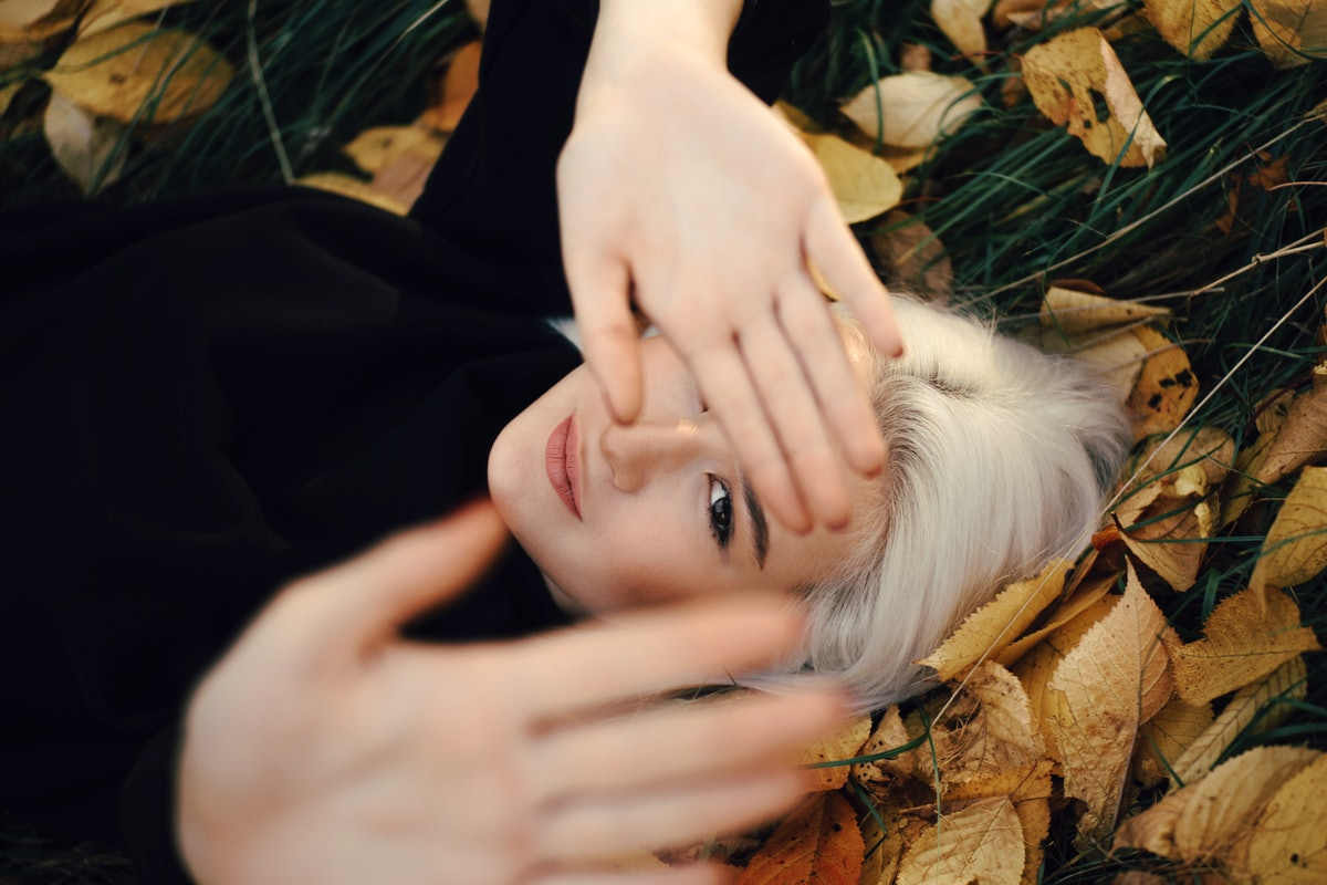 Young Blonde Woman Resting On Orange Leaves