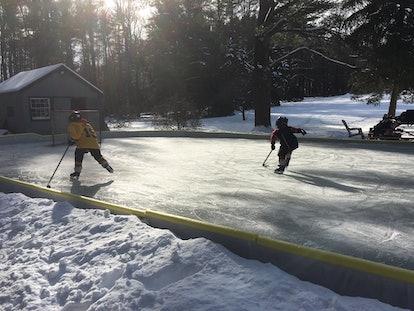 Kids play ice hokey on a backyard skate rink.