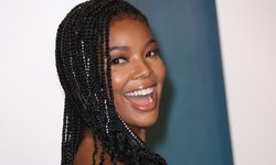 Gabrielle Union is smiling over her shoulder in a gorgeous fluffy white dress.
