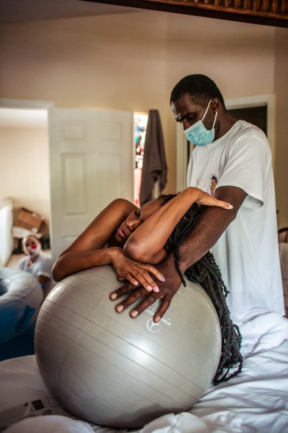 a woman labors with a birthing ball while her husband supports her as he wears a mask