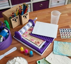 Crayola paper maker kit sitting on desk with colored pencils and craft supplies