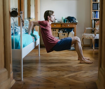 A young man using his bed to do body weight exercises at home to keep fit.