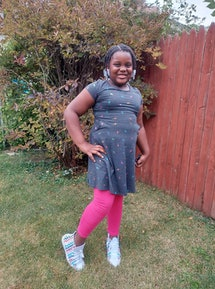 The author a 7-year-old Black girl, in ping leggings and her Converse sneakers.