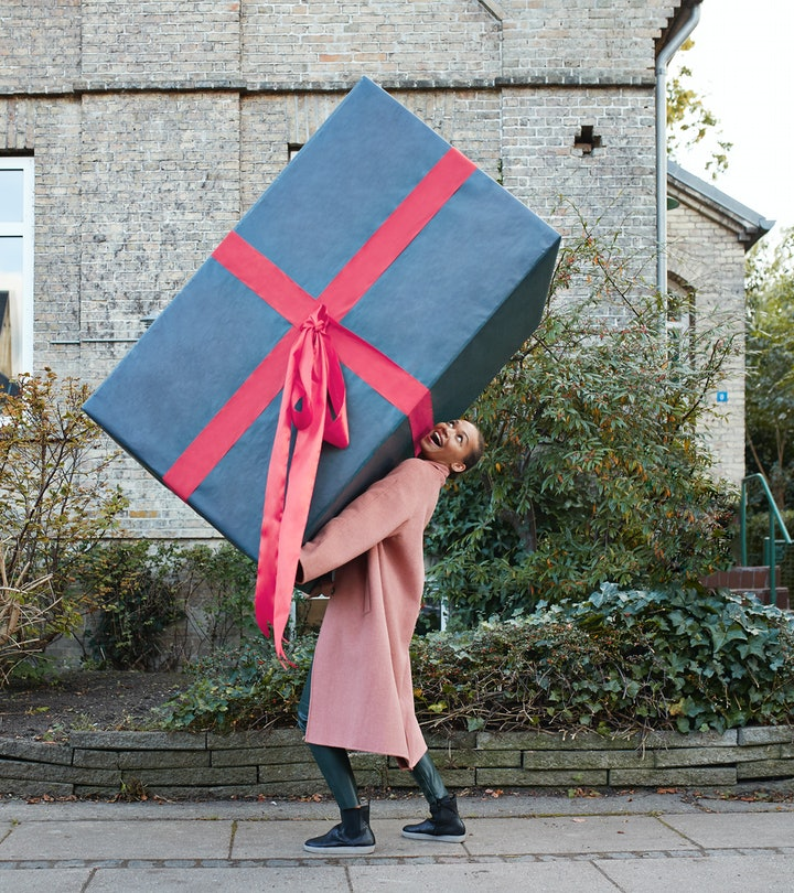 woman walking down the street carrying an oversized present