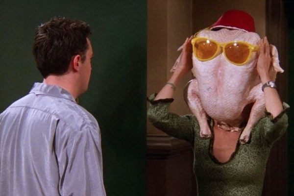 Monica (Courteney Cox) from 'Friends' dances with a turkey on her head in the doorway in front of Chandler.