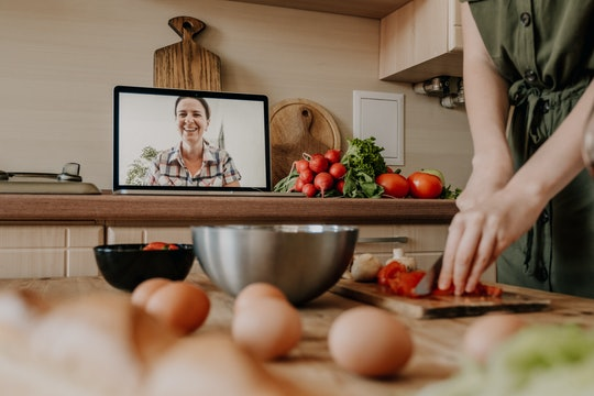 woman cooking, chopping vegetables over video chat