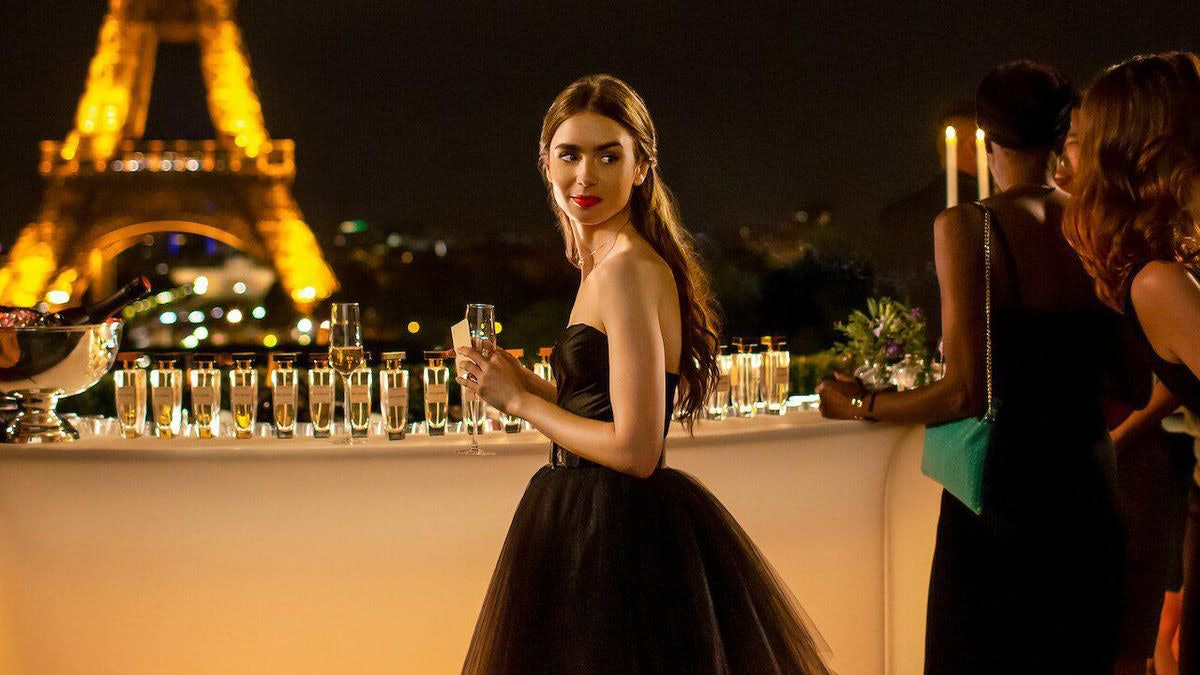 Emily (Lilly Collins) from 'Emily in Paris' stands by the bar at a party, wearing a black gown, near the Eiffel Tower.