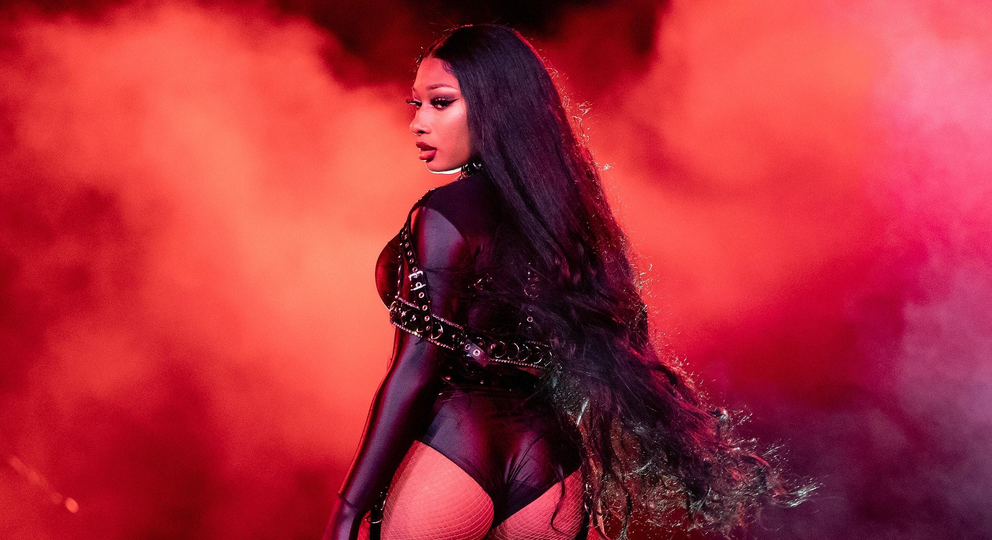 Rapper Megan Thee Stallion at a concert in front of red lights and smoke.