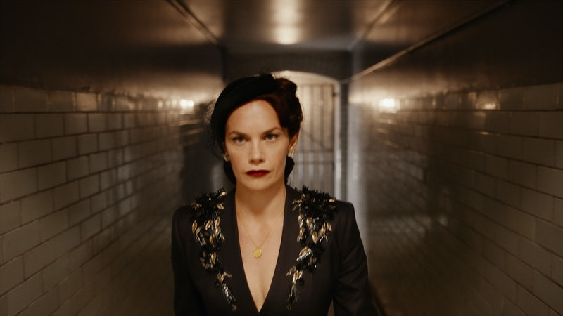 Mrs Coulter (Ruth Wilson) wearing a black jacket and hat and walking along a tiled corridor