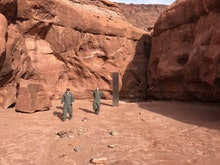 Two men approach the monolith.