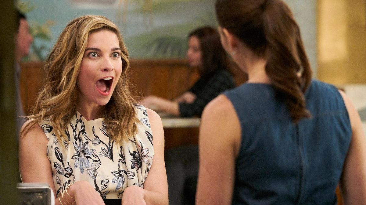 Alexis Rose (Annie Murphy) looks surprised at Twyla (Sarah Levy) while sitting at the counter on 'Schitt's Creek'.