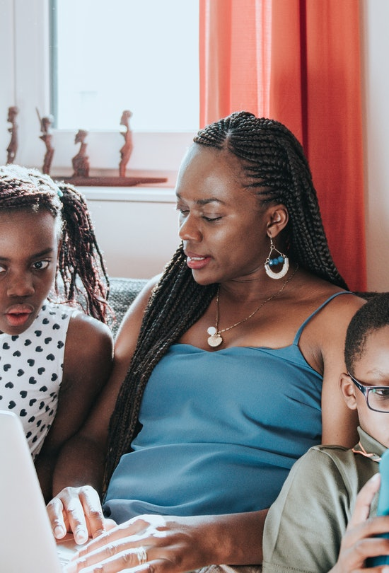 A Black mom works on a laptop; her two children sit on either side of her.