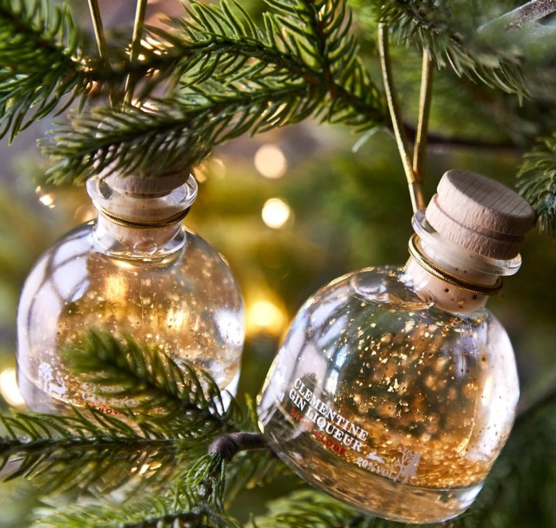 Small wood-stoppered gin bottles filled with a clear liquid and flakes of gold leaf nestled in christmas tree branches