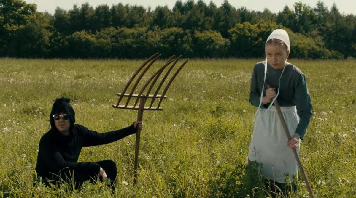 David (Dan Levy) sits in a field with an Amish girl on 'Schitt's Creek.'