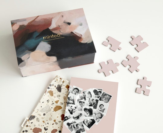 Minted box, photo, bag, and puzzle pieces scattered on a white table