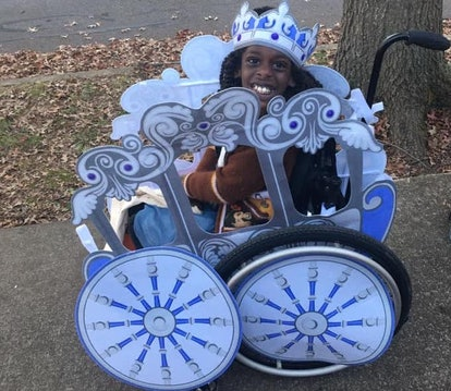 A smiling little Black girl in a Cinderella costume that turns her wheelchair into Cinderella's magical coach.