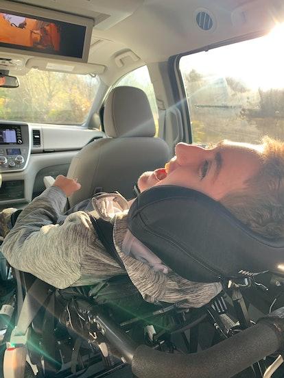child in wheelchair riding in a van