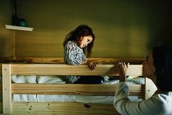 A little girl is sitting in her top bunk bed, looking at her mom.