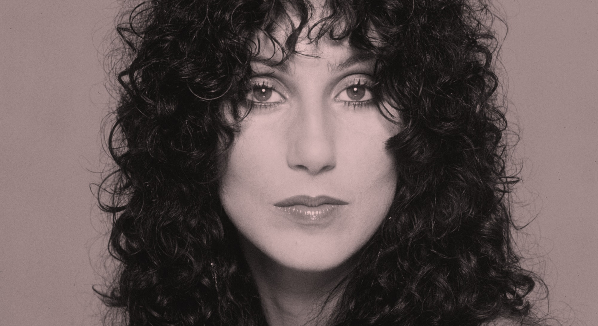 Cher with long curly hair.