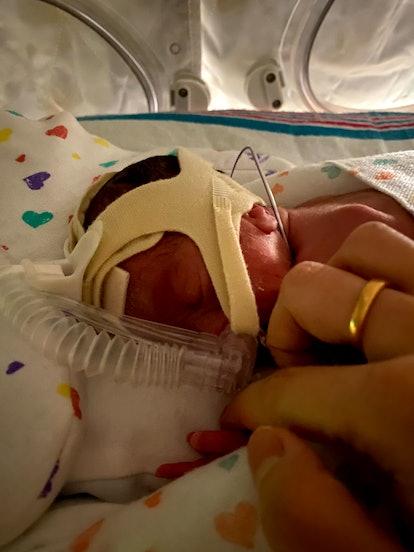 27 week old premature baby in isolette, holding mom's finger