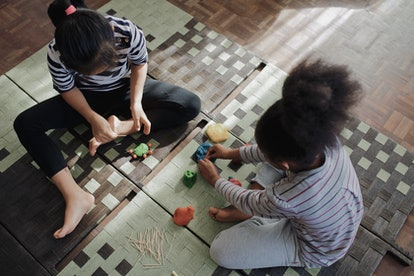Two little girls are seen from above, playing with playdo or putty on a woven mat.