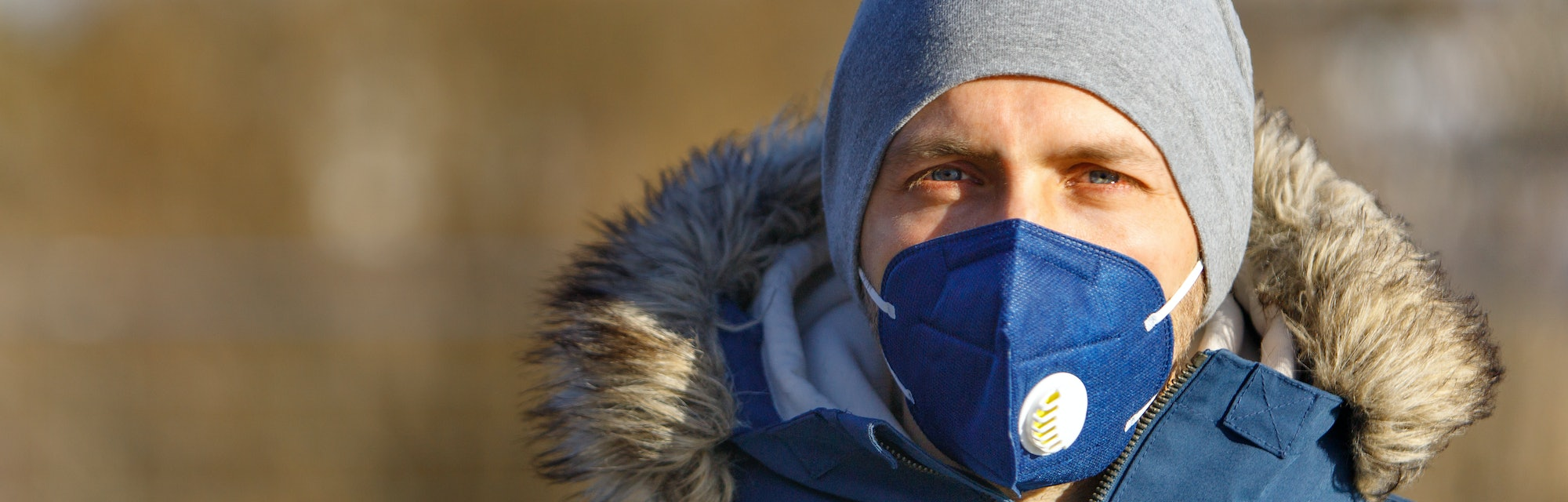 Man wearing a mask and warm clothing.