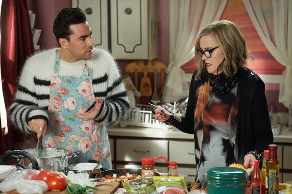 David (Dan Levy) tries to make enchiladas, while his mother, Moira (Catherine O'Hara), goes over the recipe in the kitchen.