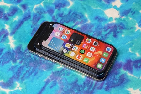 The iPhone 12 mini on top of the iPhone 12 and 12 Pro Max.