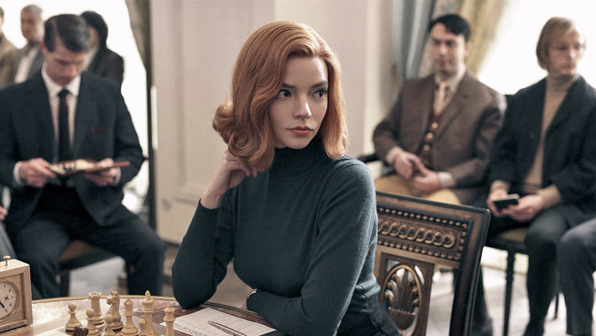 Beth (Anya Taylor-Joy) sits at a table with a chess game before her in 'The Queen's Gambit.'