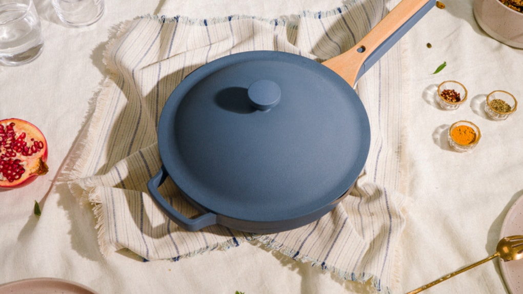 The blue salt Always Pan from Our Place sits on a dining room table with a kitchen towel underneath.